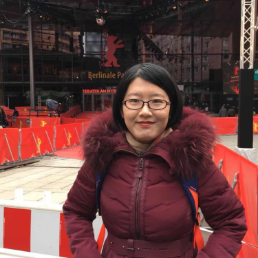 Ziying Zhang stands in front of a theater.