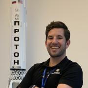 Aidan Rafferty stands by a  model of a rocket