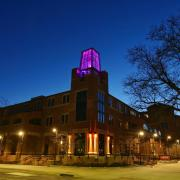 The tower of the Roser ATLAS building lit with a magenta light.