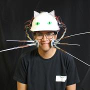 Chris Hill wearing his  Whiskers project, including a hat that looks like a cat.
