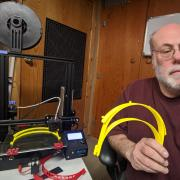Wayne Seltzer holds several face shield parts next to his 3D printer, which is making several more.