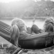 The back of heads of two young girls in a hammock by a lake.