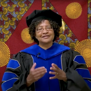 Donna Auguste giving a virtual commencement speech, dressed in graduation regalia.