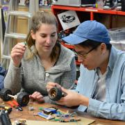 Two students smile as they build a remote control car from cardboard, salvaged parts and micro:bits