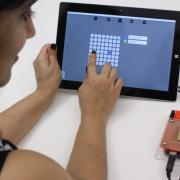 Person using a tablet to control droplets on the OpenDrop biochip