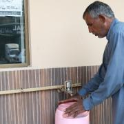 Man getting water from Water ATM