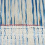 Blue and white partially woven cloth on an unseen loom.