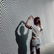 Woman stands in front of a black and white striped wall in the Moire Room at Meow Wolf Denver.