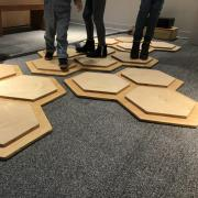 Legs of people standing on the musical hexagons.