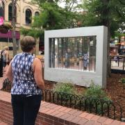 Photo of Woman looking at 'are you me' mirror sculpture on Pearl Street
