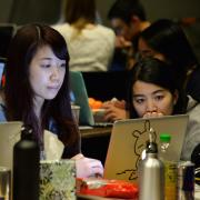 Photo of students coding together at T9Hacks
