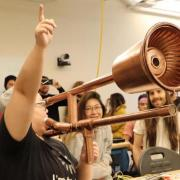 During the Moog Hackathon, Ruhan Wang demonstrates the e-trombone to the delight of other hackathon participants.