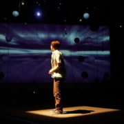 From a past show in the black box a person looks to a background that looks like planets.