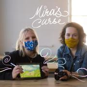 Lillie Bahrami and Emily Gould sit next to each other with masks on holding an iPad of an image from their project, Mira's Curse.