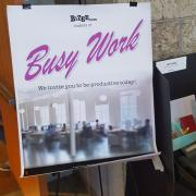 """Sign posted in an office. It says, """"Busy Work. We invite you to be productive today."""""""