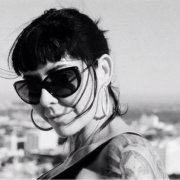 Kristelia Garcia wearing sunglasses and wind-swept hair around her face.