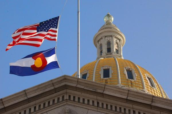 The Denver Capital building dome next to an American and Colorado State flag.