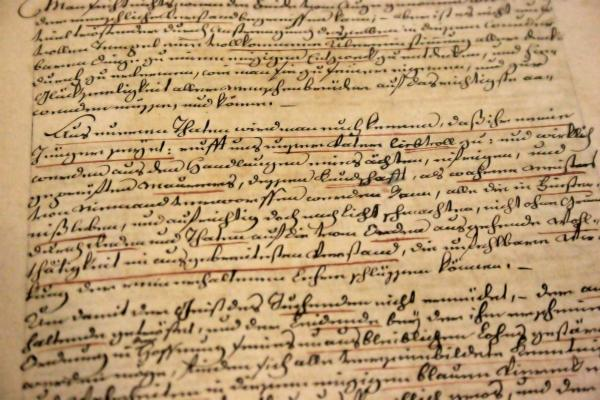 Tanned old document with cursive black and red writing.