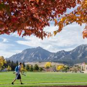 Flatirons in the fall, with a student walking by.