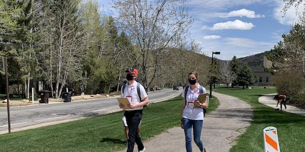 Volunteers, part of the Utah HERO project, walk down a neighborhood path.