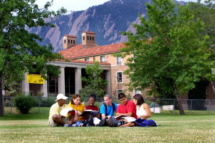 Group of students studying on the lawn on the CU Boulder campus