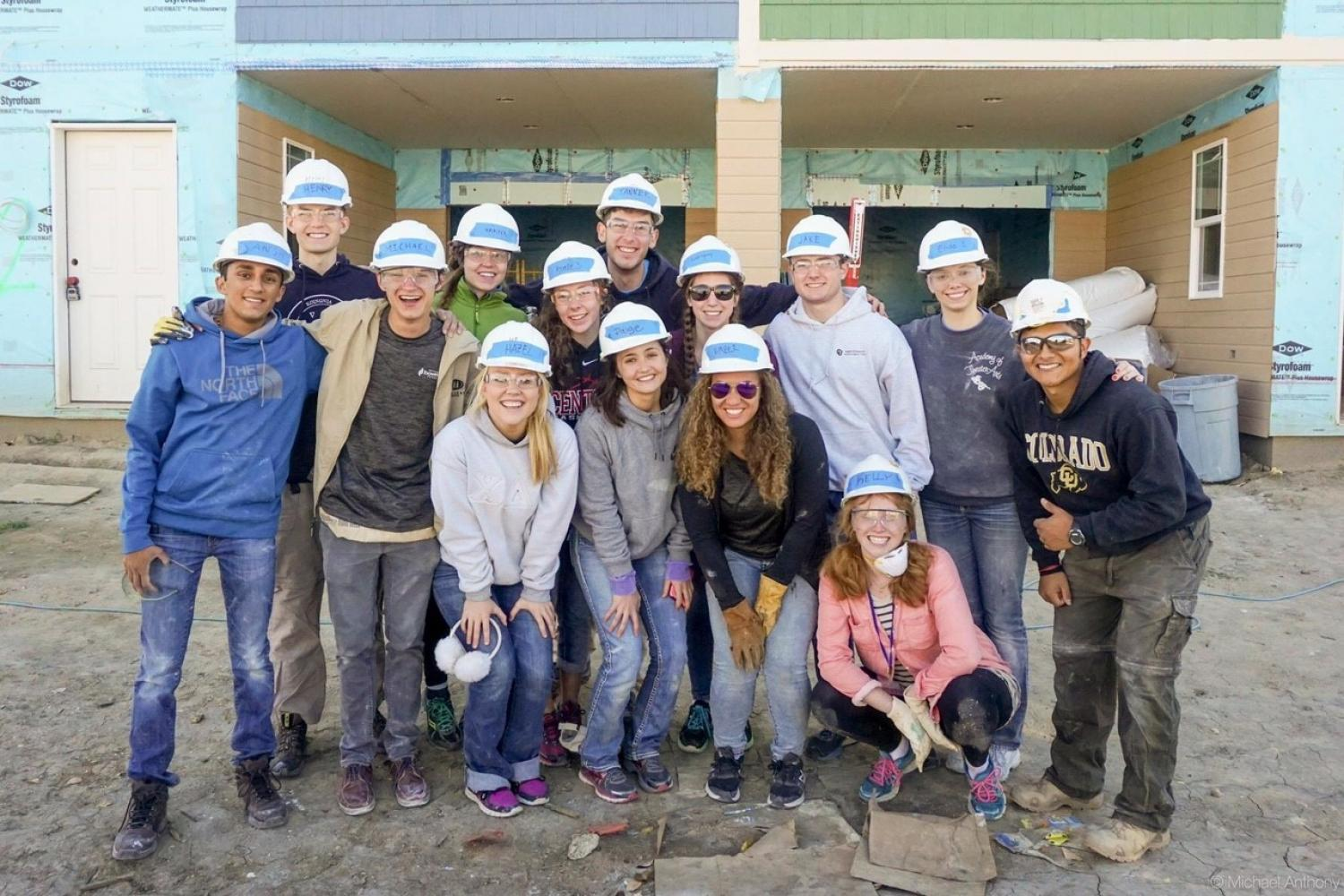 Students posing in front of a house they helped work on.