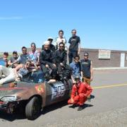Race participants sitting on one of the cars.