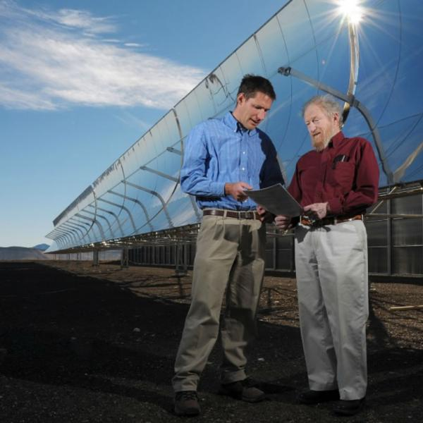 Faculty conferring near solar panels. When possible, place subjects in the field relating to their subject of interest.