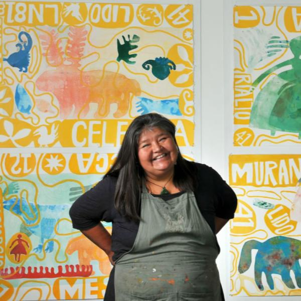 CU Boulder art professor Melanie Yazzie is photographed in front of one of her prints. Use spontaneity and interactions with your subject to create engaging portraits.