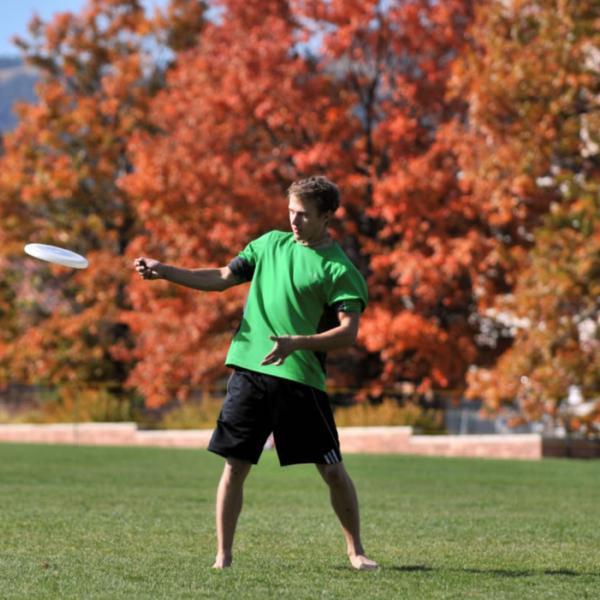 A student plays Frisbee on a fall day. Capture environment when it helps tell the story.