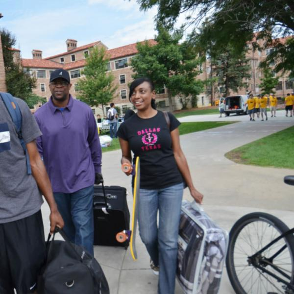 A family helps a new student on move-in day.  Capture action when possible.  Be mindful of branding or logos on shirts.