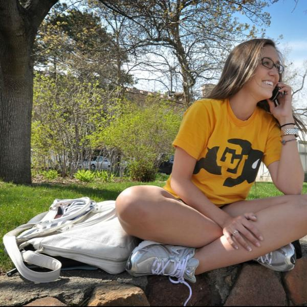 A student enjoys a spring day outdoors. CU Boulder logos are good to capture in photos.