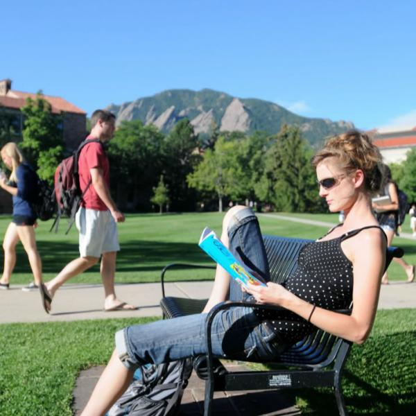 A student relaxes on a bench in the quad. A wide-angle lens provides more depth in images.