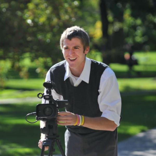 A journalism student works on a video. On sunny and contrasty days, it's best to keep subjects with their backs to the sun. The rim of light on the subject is pleasing, and they are not squinting into the light.