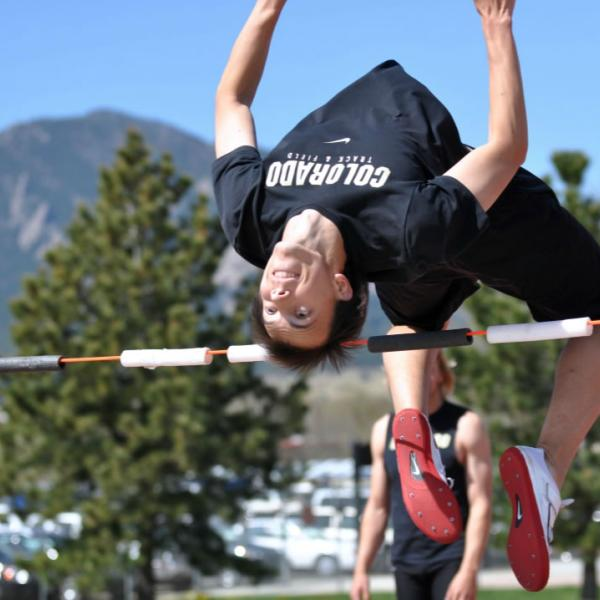 A track student participates in the high jump. When possible, frame the flatirons in photos.