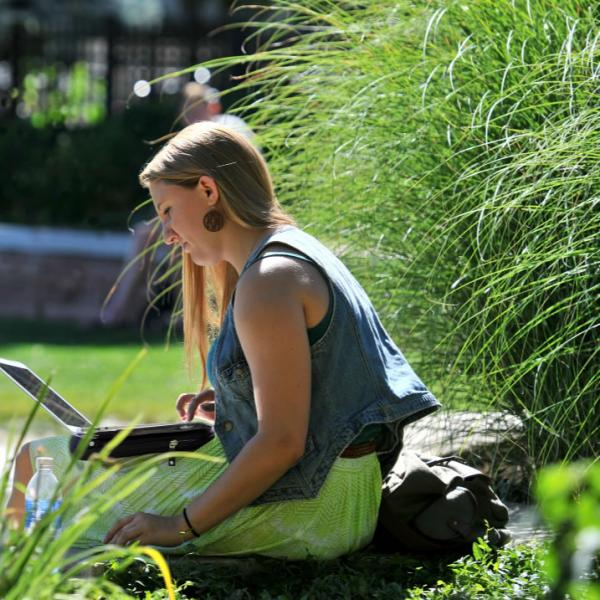 A student studies on Farrand Field. Telephoto lenses are good at compressing elements and making backgrounds go out of focus. Here also is the backlighting technique for more pleasing full-sun photos.