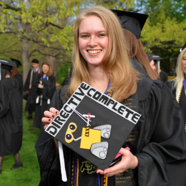 A graduate displays her decorated cap before the processional into Folsom Field. Don't hesitate to ask subjects to pose when needed.