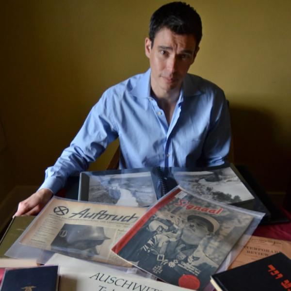 David Shneer poses with Holocaust documents. Use natural lighting and depth with wide-angle lenses to emphasize objects in the foreground.