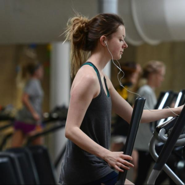A student uses an elliptical machine in the Rec Center. Use natural light and repetition of form for interesting composition.