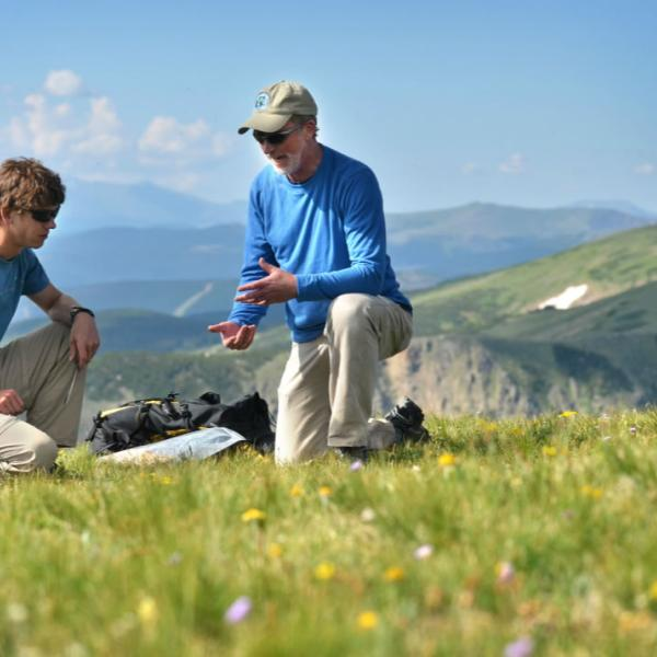 A faculty member and student work together in a mountain field conducting research. Telephoto lenses in the field help compress the background to simplify a scene and also keep you out of the way of researchers.