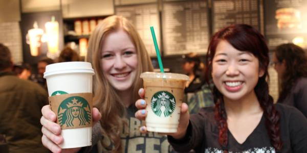 Two female students holding up their starbucks drinks