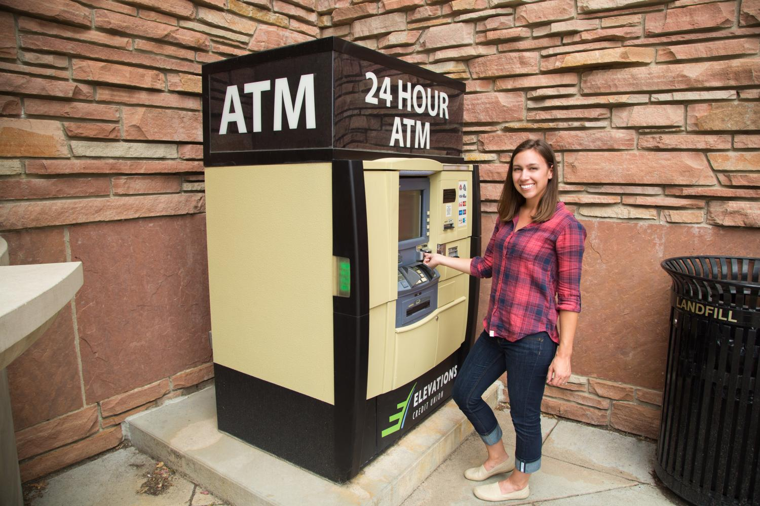 smiling woman standing at ATM