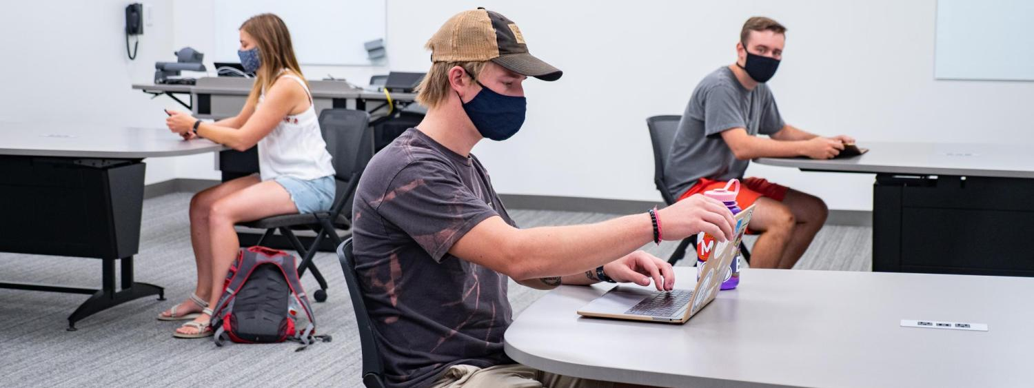 student sitting at a table with mask on opening his laptop