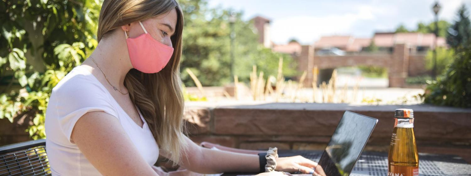 student with mask on looking at laptop