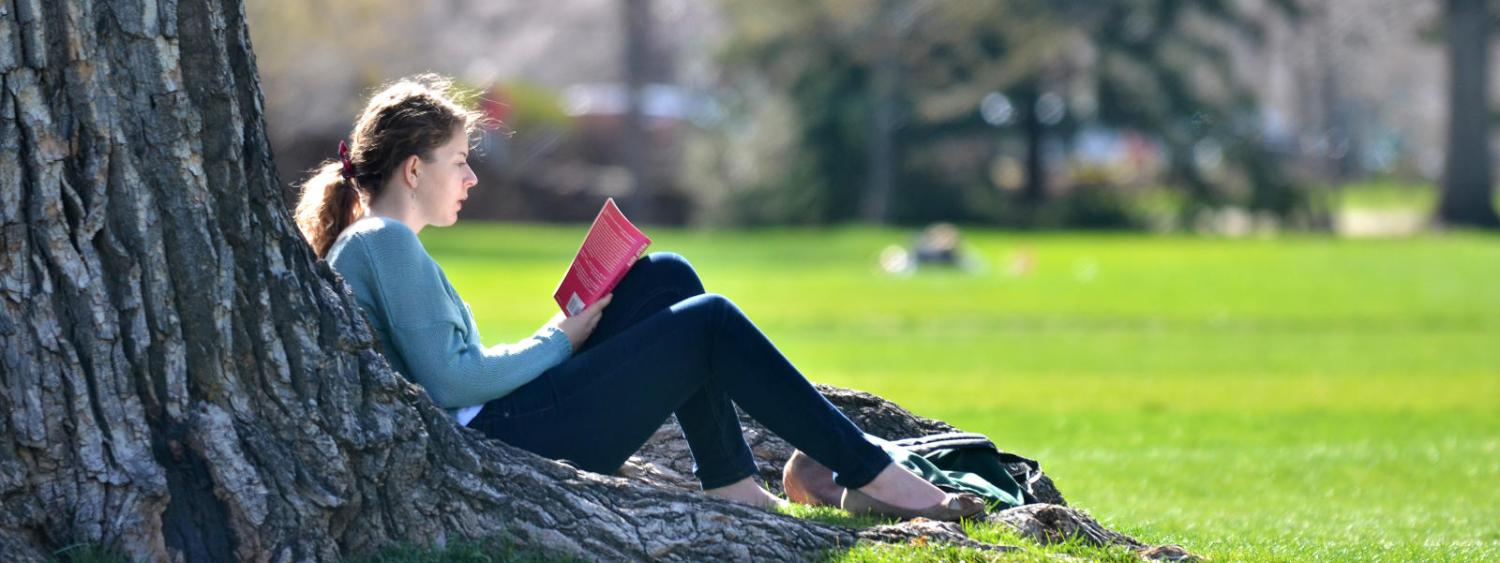 student sitting on grass reading