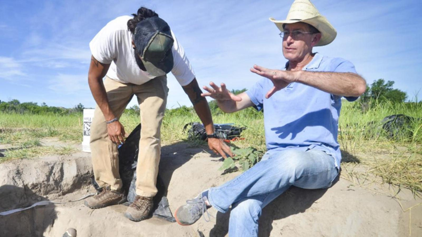 An anthropology professor and student take a break at a dig site.