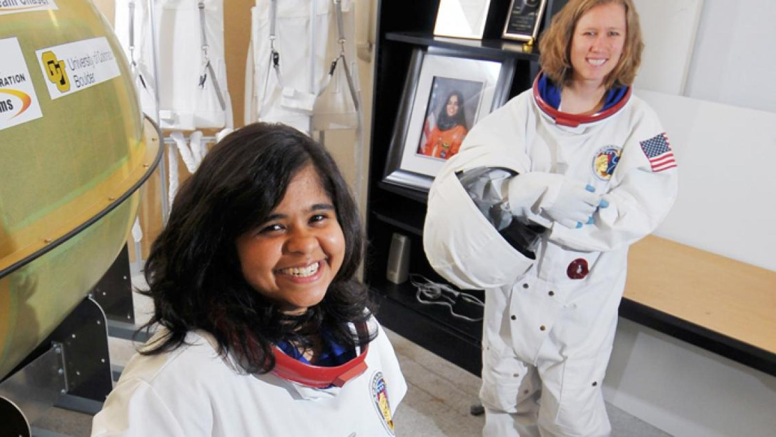 Two female students dressed in space gear get ready for a simulation.