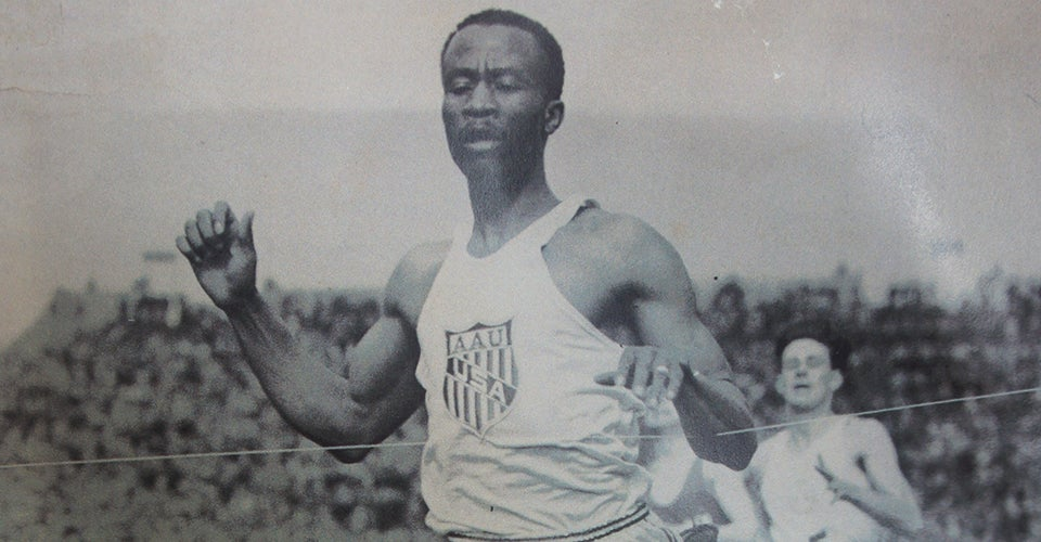A black-and-white photo of David Bolen running on a track.