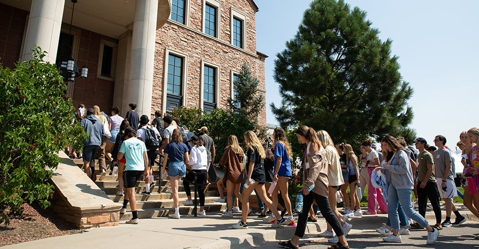 A group of first-year students walking into the Koelbel Building on a sunny day.