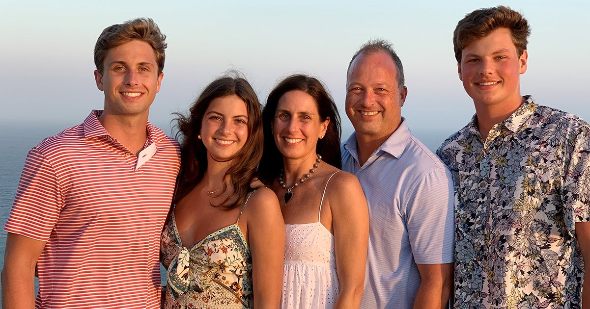 A family of five poses on a beach at sunset.